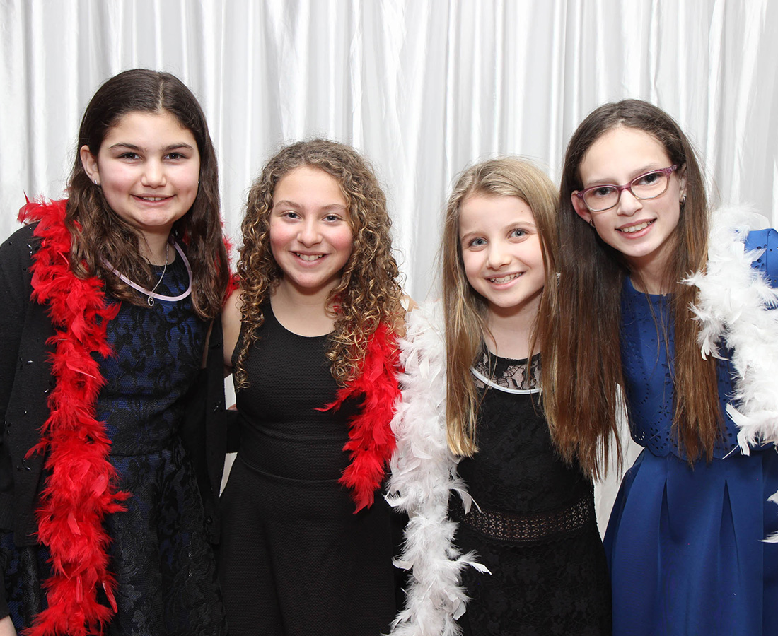 girls posing at a bat mitzvah with props